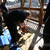 Cutting a hole in the 3rd floor porch floor. The tripod will have a block and tackle pulley with lines dropped to the pit and hooked onto both rescuers and victims.