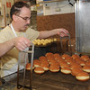 Sam Minnino pulls a load of paczki out of the deep fryer. DAVID DALTON--The Macomb Daily