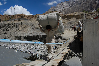 The locals carry huge sacks of aid over the flexing bridge as if it was nothing!