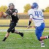 Don Knight/The Herald Bulletin<br /> Madison-Grant quarterback Dakota Brooks rolls out of the pocket and finds  tight end Drew Smith open down field for a touch down as he is pressured by Elwood's Jared Bourff on Friday.