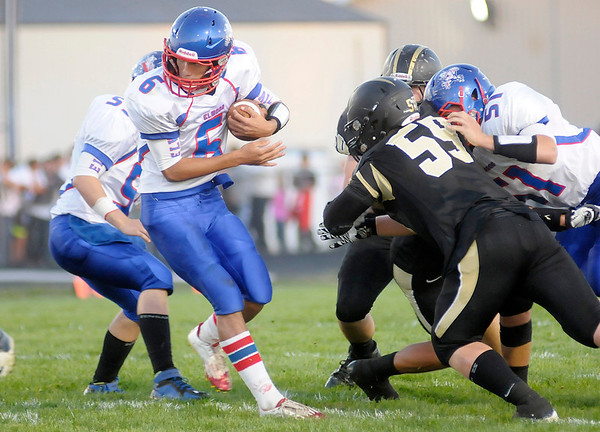 Don Knight/The Herald Bulletin<br /> Elwood quarterback Alex Mireles keeps the ball for a run up the middle against Madison-Grant on Friday.