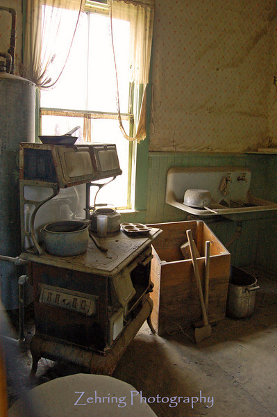 "The interior of abandoned homes strangely left intact as the inhabitants of Bodie, CA seemed to have simply left - as if overnight - leaving all their belongings, even glasses and cooking utensils where they sit to this day in the ""ghost town"" now protected by the state of California."