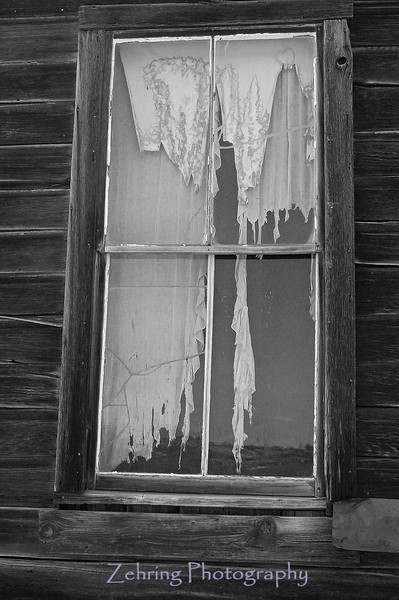 """Decaying curtains in the window of an abandoned home in the """"ghost town"""" of Bodie, CA."""
