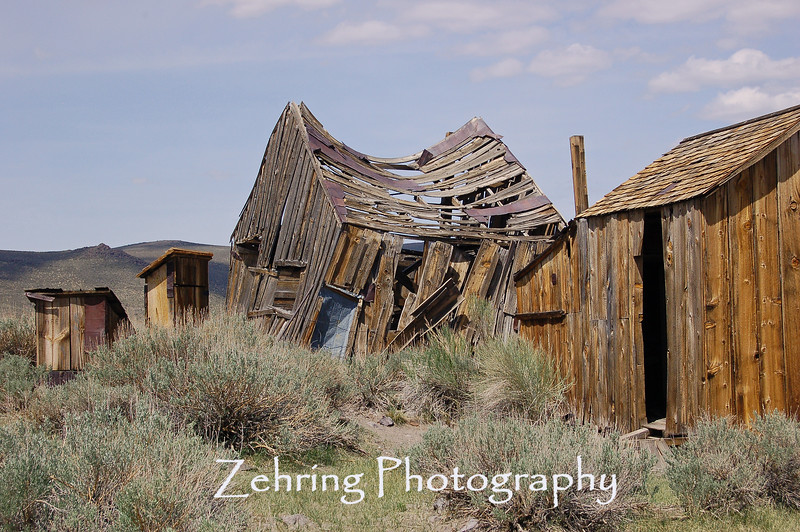 Soon this abandoned home will collapse in decay while the out-house to the left remains standing. Bodie, CA.