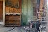 "Once a living room, now a ""dead room"" furnished with a bookcase and a few remaining books, a woodburning stove, a decaying old couch, complete with wall-to-wall carpet and peeling wall paper. All the comforts of home! Bodie, CA."