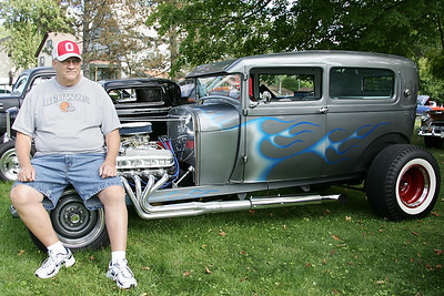 """Frank Stramowski with his 1928 Ford Hotrod. While many of the cars at the show maintained rigid authenticity, Frank has made a number of enhancements to the 1928 Ford. Racing seats, open wheels, and 9"""" frame extension allowed room for a big block engine -which helps him cover 1/4 mile in the mid 12 second range with a 106 mph finish. A Mustang front end allows for a better ride and stability on the highway. """"It's like the hotrods we drove in the 60's"""" he says. """"I'm 18 again went I get in."""" photo by Ray Riedel"""