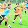 Tiarra Spencer (left) tries to maneuver past defender Kyla Kenyon as the Tupper Lake varsity girls soccer team work out in preparation for their season opener Sept. 7 in Malone against Franklin Academy. <br><br>(P-R Photo/Pat Hendrick)