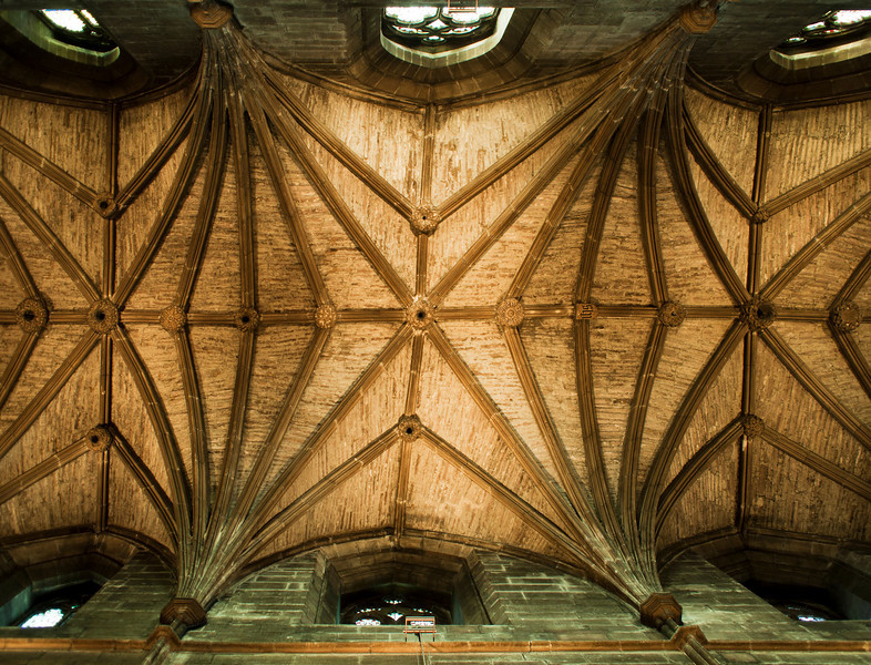 The stone ceiling over the nave of St. Giles Cathedral in Edinburgh, Scotland is criss-crossed with stone work to support the roof. With details illuminated by window light, the atmosphere is quite warm on the inside.