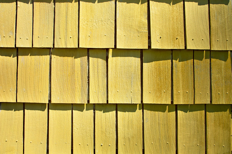 Weathered old yellow shingles on an outside wall of a house form an abstract pattern.
