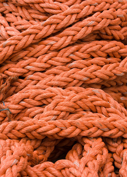 An orange rope all heaped together on a dock in the Victoria and Albert waterfront in Cape Town, South Africa. Lines like these are used to tie up ships at the pier.