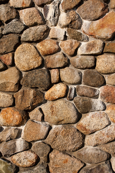 A pattern created from the exterior wall of a fireplace made of rounded rocks from an old river bed.