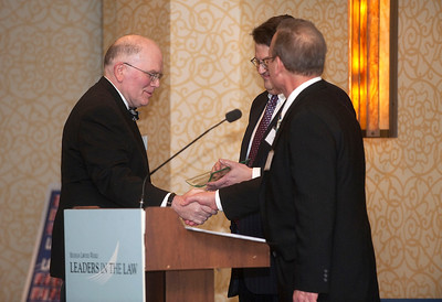 Paul McKenney accepts his Leaders in the Law award from Editor Gary Gosselin and publisher Paul Fletcher in Troy, MI on March 21, 2013.