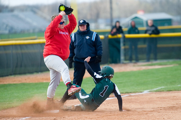 During the second inning Elwood High School third baseman Jessica Taylor catches the throw to get Pendleton Heights High School base runner Heather Wendling out. Pendleton Heights High School defeated Elwood High School in the Madison County softball tournament championship game Saturday, April 13, 2013. Photo by Richard Sitler
