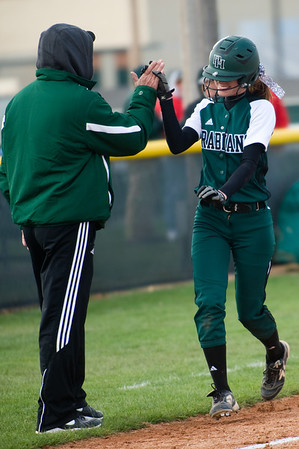Pendleton Heights junior Sarah Dixon is all smiles as she slaps hands with the third base coach as she rounds the bases after hitting one over the fence for her first home run of the season. Pendleton Heights High School defeated Elwood High School in the Madison County softball tournament championship game Saturday, April 13, 2013. Photo by Richard Sitler