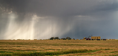 Bringing in the hay - it's harvest month in Alberta - and a storm is also approaching. The wind in this storm was fierce - rain swept across the highway like drifting snow. Sept 2012.