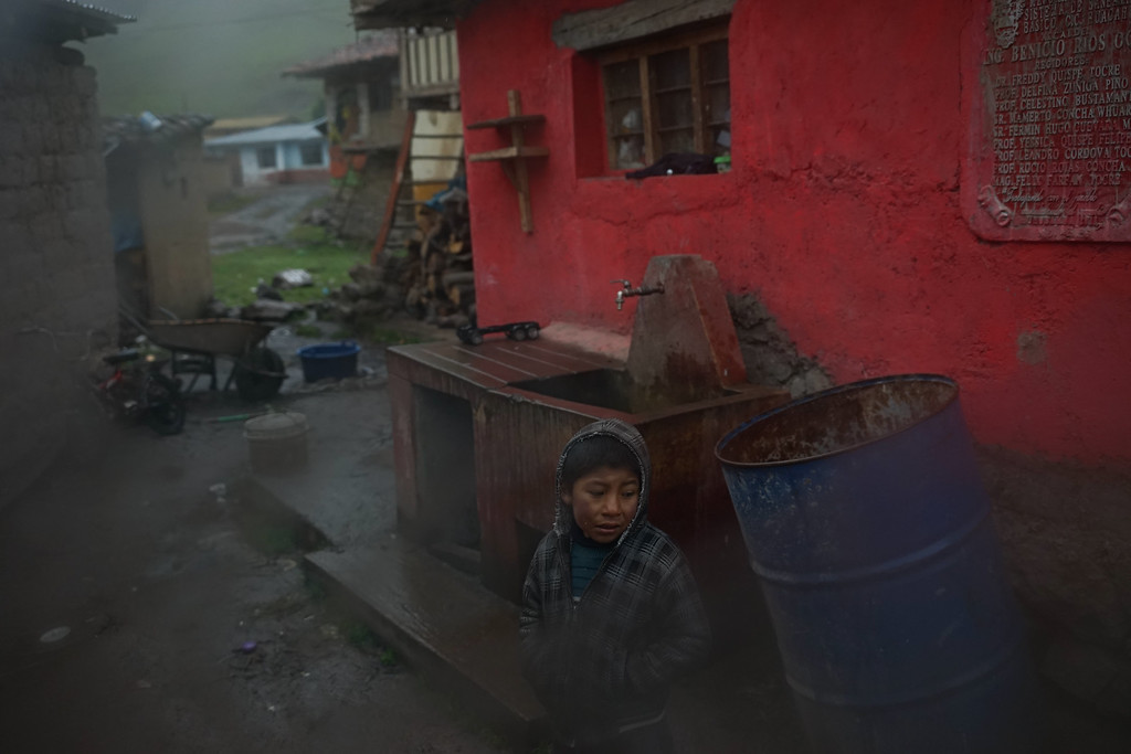 A boy watches our vans come through the muddy streets to the school.