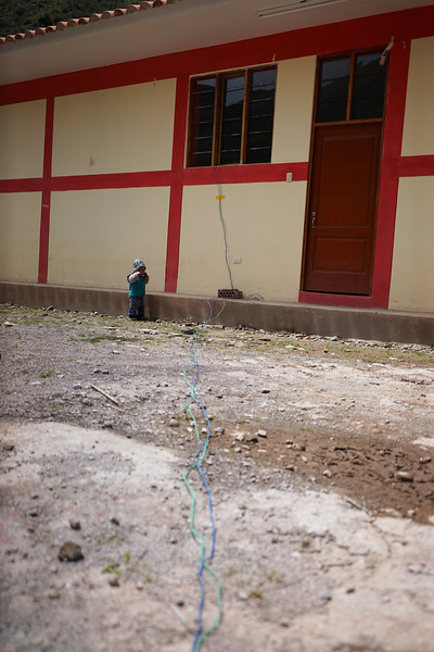 The village provides us with electricity so we can charge our cameras etc. This is how they do it. This wire ran over the water and into the school. It sparked and sizzled. But worked!. And yes, that is a little child.