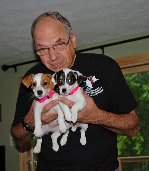 Ray has two doggies in his hands.