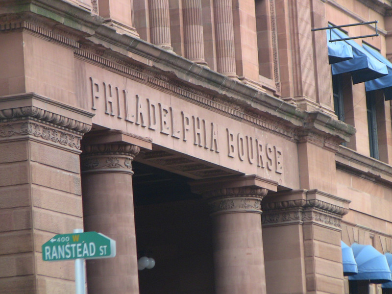 The Philadelphia Bourse Building, the first commodities exchange in the United States, was completed in 1895. The building was one of the first steel-framed buildings to be constructed. Three types of masonry were used on the facade: Carlisle redstone, Pompeian buff brick and terra cotta. Inside were large columns and pilasters leading to a balcony surrounding the main floor. Bow-top girders were used to support a skylight at the third floor.