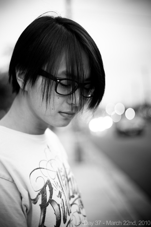 """Today, I had a nice phone conversation with him before sleeping until noon. Later, I went out with Kaeo and Reid working on my Top Ten for Metromix. At one point I wanted to play with the bokeh in the early evening light, so I told Reid to stand on the side of the street and looke """"emo""""."""