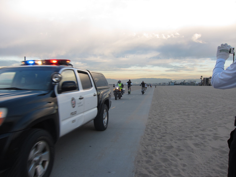 Police in front of the first elite runner, Moses Waweru  Photographer's Name: Mary Fasang Photographer's City and State: Redondo Beach, CA  To vote in favor for this photo, simply add a comment below. You can also share this photo on Facebook and Twitter using the buttons above.