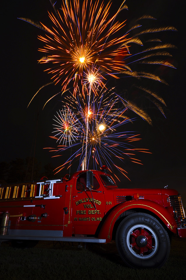 "4th of July,   Hollywood VFD had a very nice 4th celebration at their firehouse.  They held a car show, a band, and fireworks.  John mentioned getting the firetruck and fireworks in one shot, and I tweaked things a little to get this image.  I really wasn't that excited about shooting this evening.  We were supposed to shoot for the production group at the Trace Adkins concert, but once there were told ""no cameras on the in field'.  So instead of shooting from the stands, 120 feet away, we left.   Oh well, I got a cool shot of a firetruck on the 4th instead!  I'm happy."