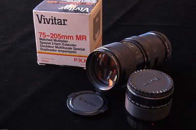 Vivitar 75-205 f/3.8 with matched 2x teleconverter. Manual focus, preset aperture.  There is some minor wear and brassing and on the body, but nothing unusual for a lens of this age. The glass is in very good condition - there are some tiny spots on the coating which do not affect IQ at all. Aperture is snappy and oil-free. Lens comes with original front and rear caps.  The teleconverter is in like-new condition, only used twice. It comes with all the original packaging, caps, and leather case.
