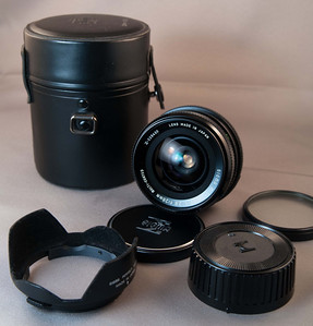 This is a Sigma Mini-Wide (version 1) 28mm f/2.8 fixed focal length lens. It has a Pentax PK/M bayonet mount. The glass is in pristine condition, cosmetically it is in very good condition. There is a bit of gunk/stickiness where the inspection sticker came off, otherwise it's very good. Focus is very nice and smooth, aperture is snappy. Comes with original front and rear caps, Sigma Perfect Hood (slip on hood), and dedicated hard case.