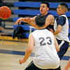Nick Martinez, back center, makes a pass while being double teamed by Josh Lucero, back right, and Mario Herrera, number 23, during boys basketball practice at Santa Fe High School on Nov. 23, 2009.          Luis Sanchez Saturno/ The New Mexican