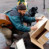 Clay Lynch, 35, from Eureka Springs, Arkansas with his dog, Taylor, makes a sign on the Plaza asking for donations to save his bus in Santa Fe, N.M. on Dec. 7th, 2009. The bus has been booted because he has acquired $194 worth of parking tickets. <br /> Leigh Fagerstrom/The New Mexican