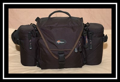 The Lowepro Off Road - this is a 'beltpack' style bag from Lowepro. Build quality is as you would expect from Lowepro, and I'd have no trouble recommending this bag.  I have also got a Micro-Trekker200, but I find this a better carry-round bag. The main bag has two seperate main compartments, and a further two detachable lens cases on the sides.