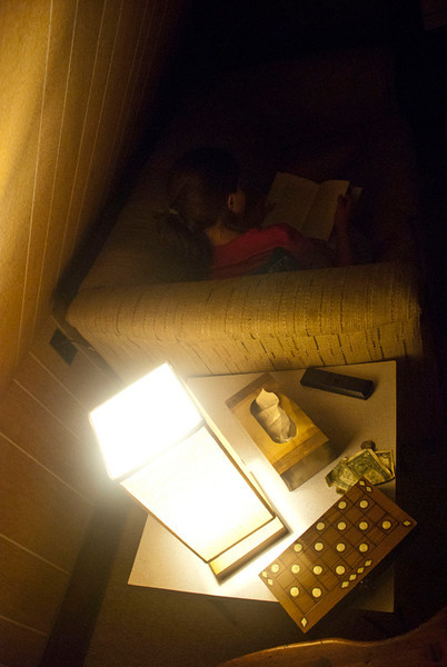 Day 4: In a hush, Dustin observes and documents his beloved ally as she reads in the soft illumination within their humble abode. All is well in the Friesen household.