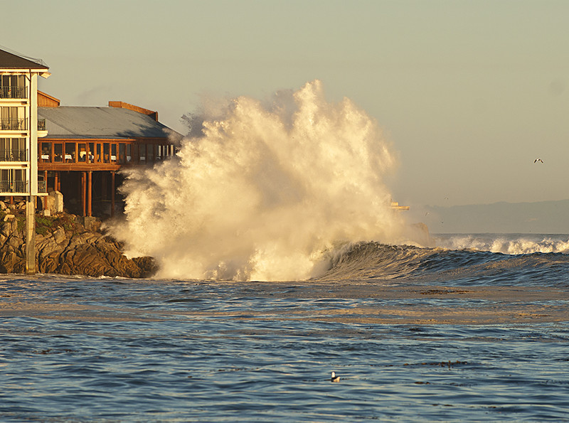 Waves crashing over rocks at the Chart House, Cannery Row,  Monterey,  Ca.