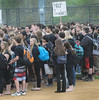 Perkiomen Valley High School students stand on the baseball field and listen to classmates speak on the elimination of teaching positions at the school. Students walked out  of morning classes in protest of the cutbacks. Photo by John Strickler The Mercury
