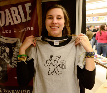Ed Burke - The Saratogian02/22/14 Hannah Sloboda of Brown's Brewing holds up a favorite shirt during Saturday's Saratoga Beer Summit at the city center.