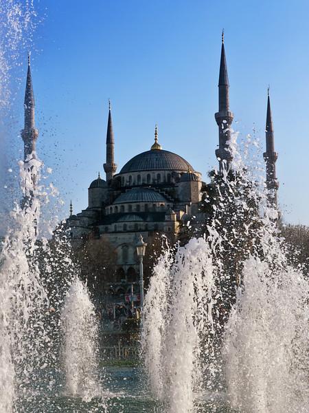 Blue mosque behind splashiing fountains