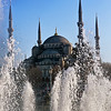 Blue mosque behind splashiing fountains