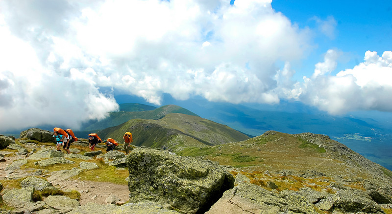 Another group of hikers climb from the ridge to Mount Monroe.