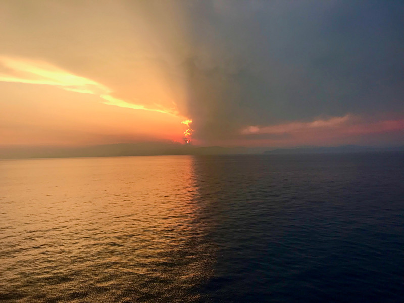 The sun sets over the Mediterranean, half obstructed by clouds.
