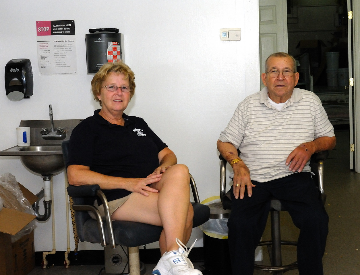 Donald Fisher and daughter Cindy occupy a corner of the Fisher's popcorn operation, while it looks like they are relaxin'... nothing could be further from the truth, they are watchin a small army of workers serve their product to the boardwalk traveler.....and making sure everything is just right!