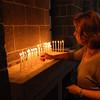 A pilgrim lights candles at St. Giragos Church.