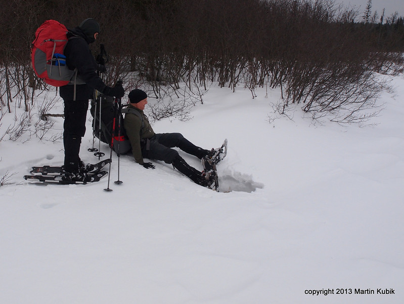 The key is to react fast, assume you broke through ice, fall toward the shore, and extricate the snowshoes quickly.  That can be tricky, because the first time it happens, our inclination is to pull the snowshoe forward and up.  Instead of hooking the toe under snow, one needs to back up the snowshoeand then lift up.  That is lot easier to say than actually do it!