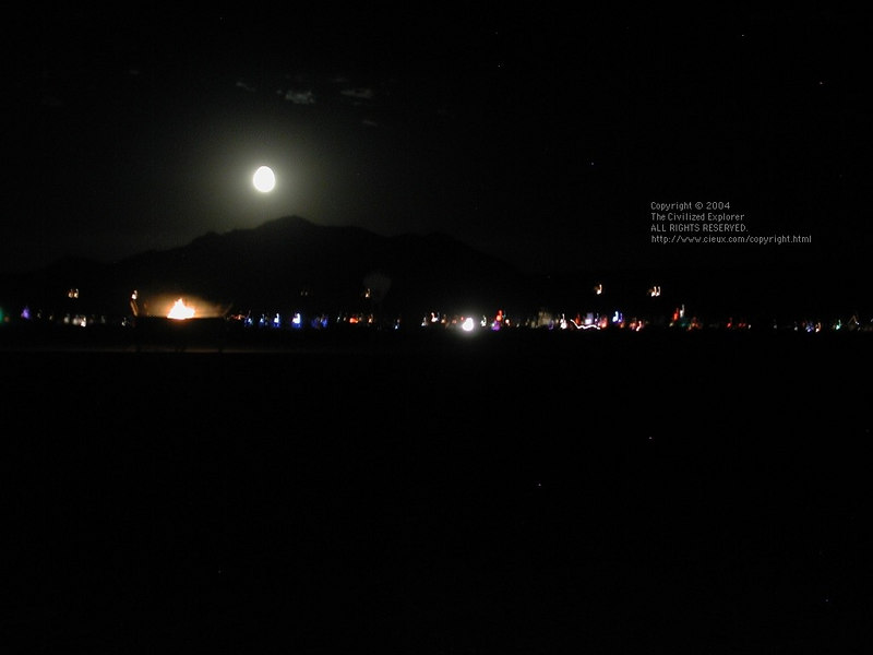 The moon rises over the mountains and Black Rock City.