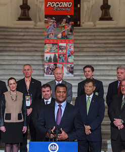 Marcus Jadotte, VP of Public Affairs and Multicultural Development, NASCAR speaking at a press conference in the PA Capitol Rotunda on March 10, 2014. Standing Left to Right - Sen. Lisa Baker; Rep. Sid Kavulich; Brandon Igdalsky, President & CEO of Pocono Raceway; Rep. Mario Scavello; Rep. Jerry Stern; C.J. O'Donnell, Chief Marketing Officer, Hulman Sports; Rep. John Payne; and Sen. Tim Sollobay