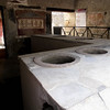 A partially restored roman kitchen in Pompeii, showing the color and the frescoes..Along with the Travertine and tiled kitchen...Clay pots were used to cook and keep food hot.