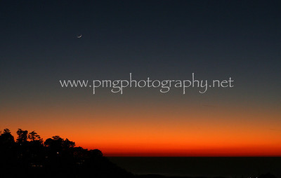 A crescent moon appearing the in the San Francisco sunset