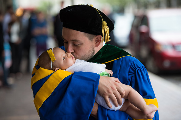 Tyson Olson kisses his 4-month-old baby, Hunter in front of Kodak Hall after the ceremony. //  Kodak Hall with his diploma. // University of Rochester School of Medicine and Dentistry Commencement, Kodak Hall at Eastman Theatre May 16, 2014.  // photo by J. Adam Fenster /