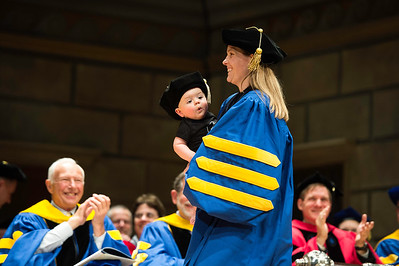 Sarilyn Ivancic crosses the stage with her 8mo son Henry during the University of Rochester's Doctoral Degree Ceremony in Kodak Hall at Eastman Theatre May 16, 2015. Ivancic's husband Steven followed immediately after her. // photo by J. Adam Fenster /
