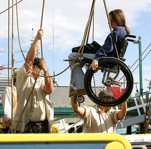 Tall ship Lady Washington crew hoisting passenger aboard the old fashioned way.