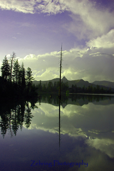 A thunderhead reflects in this alpine lake in the Tamarack Wilderness area of the Sierra Nevada range.